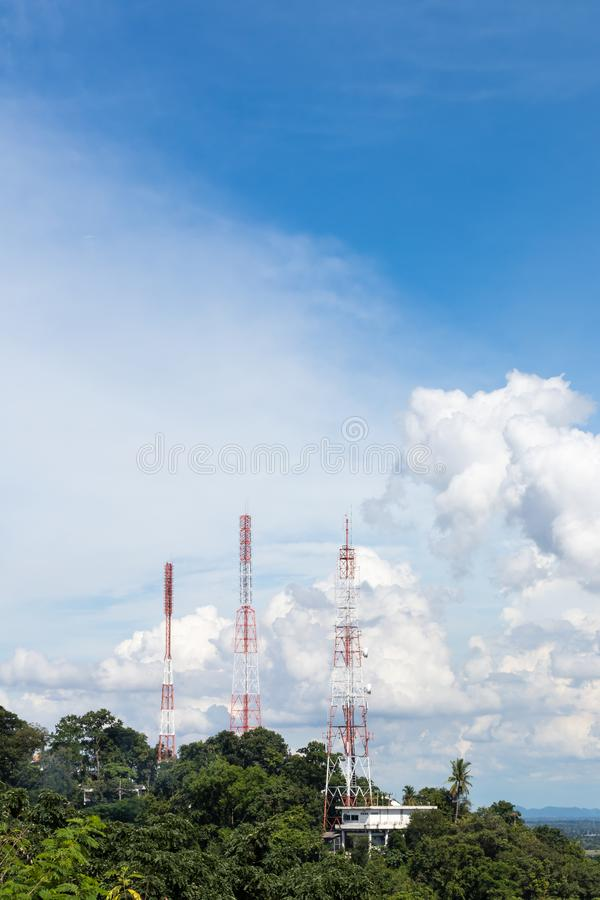 Telecommunication towers in the mountain bush. The telecommunication poles view is mounted on a tall tree bush with sky clouds as a backdrop during the day royalty free stock image