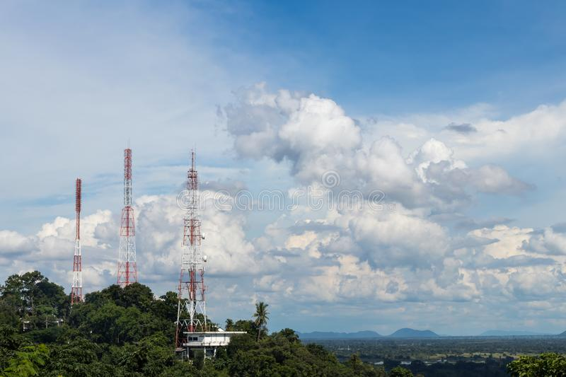 Telecommunication towers in the mountain bush. The telecommunication poles view is mounted on a tall tree bush with sky clouds as a backdrop during the day royalty free stock photo