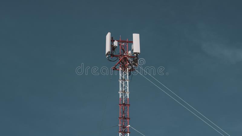 Telecommunication radio mobile tower antenna on the vast blue sky background. Transmitter internet global telephone equipment.  royalty free stock photos