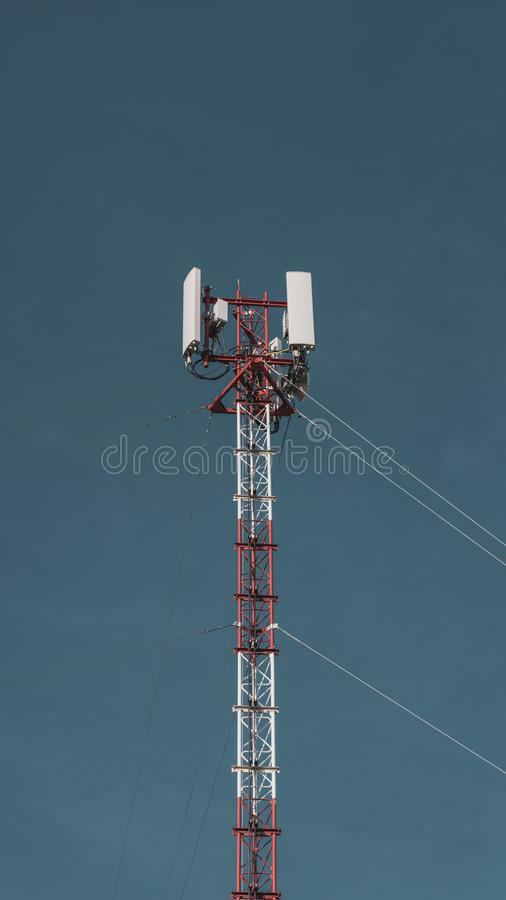 Telecommunication radio mobile tower antenna on the vast blue sky background. Transmitter internet global telephone equipment. Vertical photo stock images