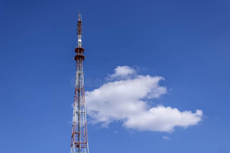 Telecommunication radio tower on the vast blue sky background. White clouds on sky stock images