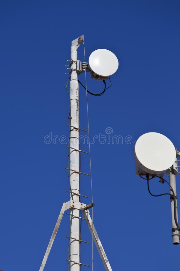 Telecommunication tower. With antennas against blue sky stock photography