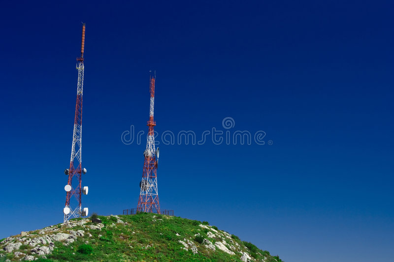 Telecommunication tower. On the green field with blue sky royalty free stock images