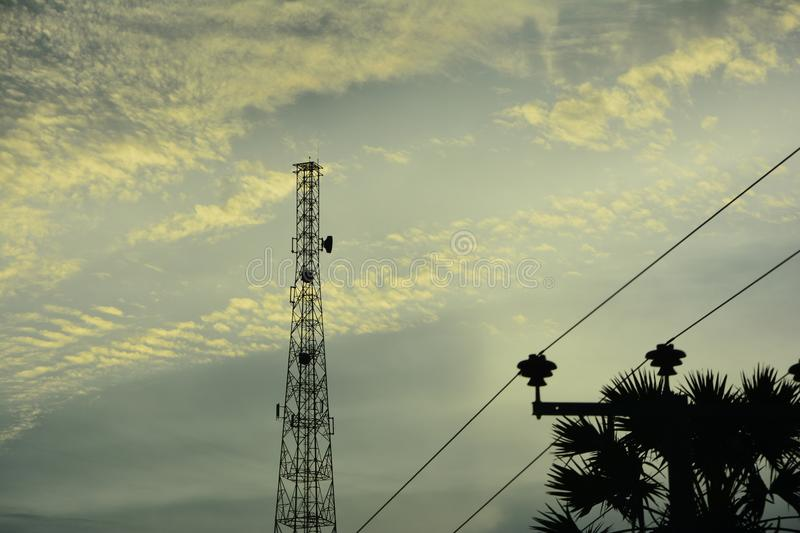 Telecommunication tower. Against the clouds, illuminated by the setting sun stock photo