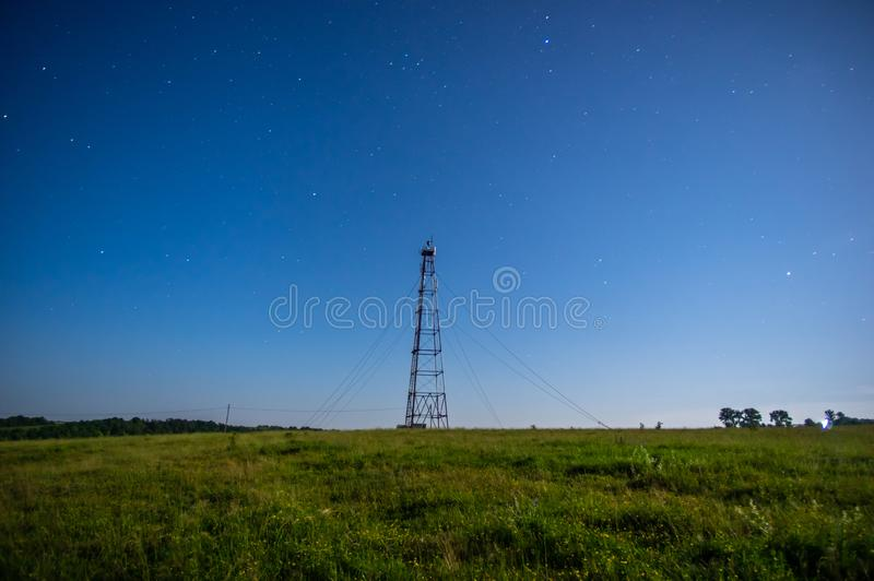 Telecommunication tower against the starry sky in the field. Telecommunication tower on a background of the starry sky in a field in summer stock image