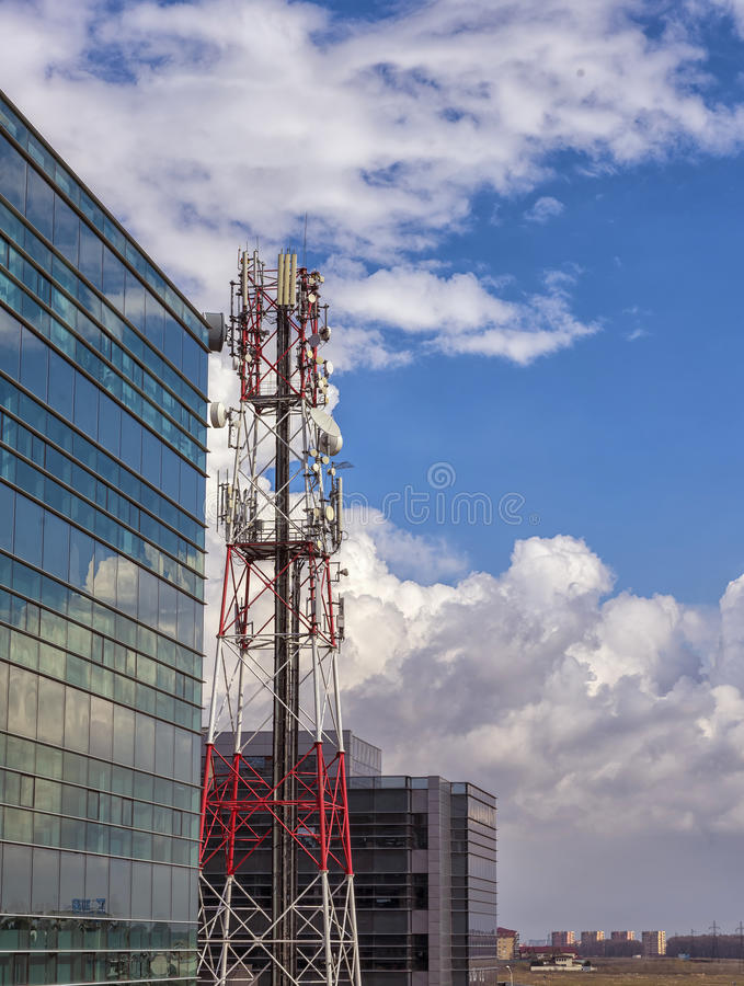 Telecommunication tower antenna and modern tall buildings. Telecommunication tower antenna and tall buildings with large clouds in the background stock images
