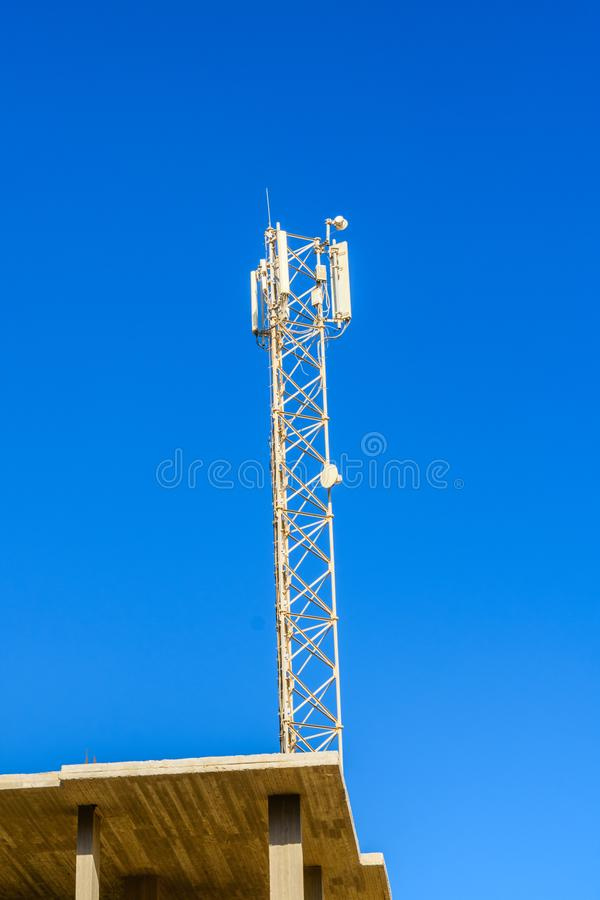 Telecommunication tower with the antennas or wireless Communication antenna transmitter against blue sky. Telecommunication tower with antennas or wireless royalty free stock photo