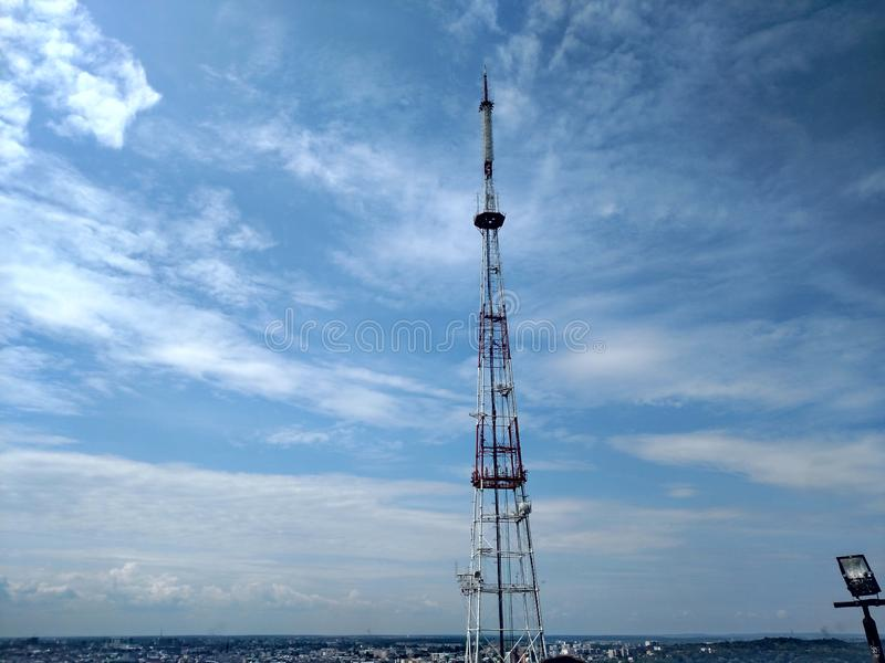 Telecommunication tower blue clouds on blue sky background royalty free stock photo