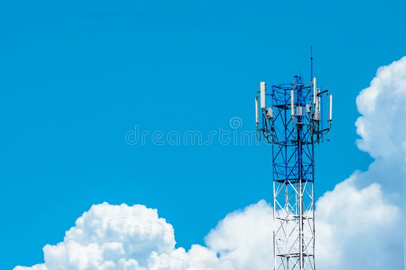 Telecommunication tower with blue sky and white clouds background. Antenna on blue sky. Radio and satellite pole. Communication stock image