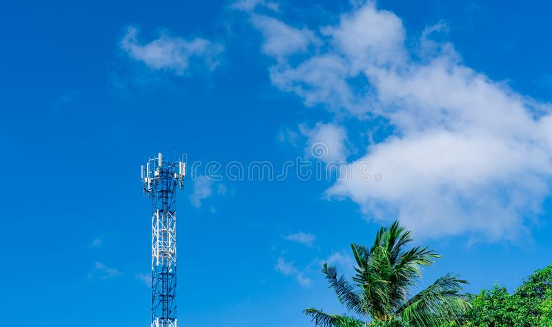 Telecommunication tower with blue sky and white clouds background. Antenna on blue sky. Radio and satellite pole. Communication royalty free stock photography