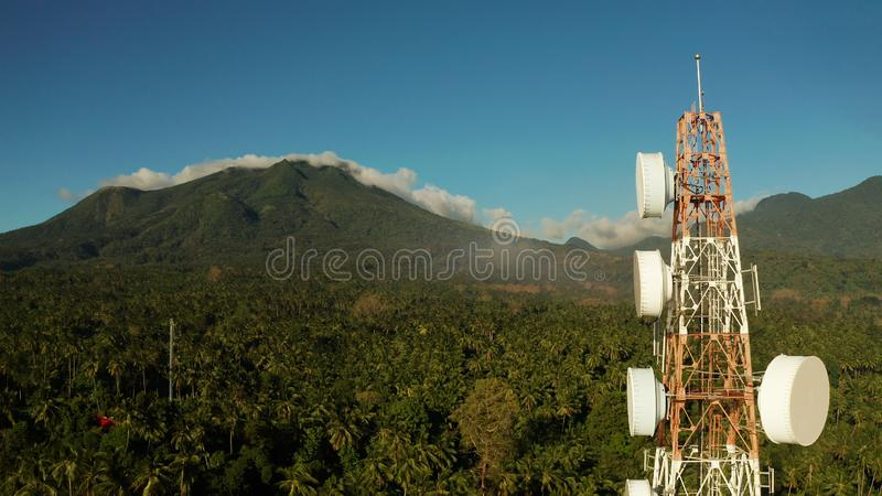 Telecommunication tower, communication antenna in asia. Telecommunication tower, communication antenna against mountains and rainforest, aerial view. Repeaters stock photo