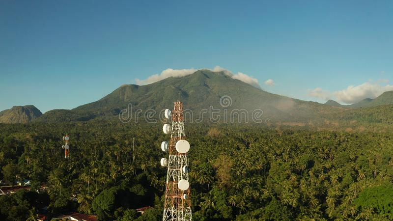 Telecommunication tower, communication antenna in asia. Telecommunication tower, communication antenna against mountains and rainforest, aerial view. Repeaters royalty free stock photo