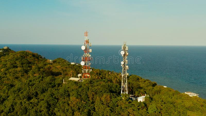 Telecommunication tower, communication antenna in asia. Telecommunication tower, communication antenna in tropical island aerial view. Repeaters on a metal tower stock photography