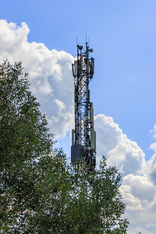 Telecommunication tower with electronic equipment on a blue sky with white clouds background against green tree royalty free stock photography