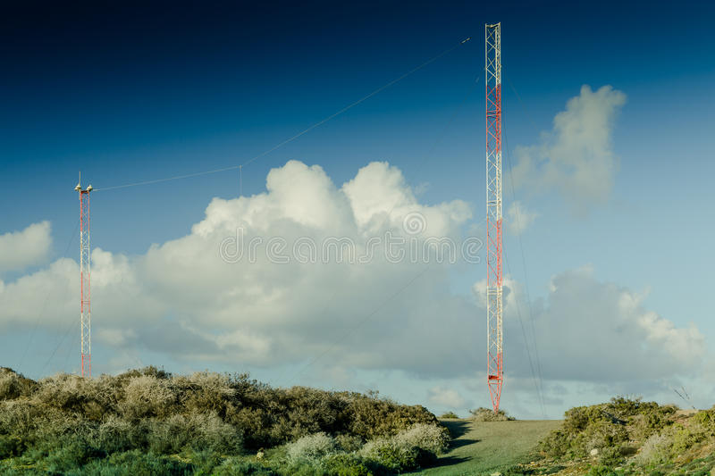 Telecommunication tower in the field. Against a blue sky royalty free stock photography