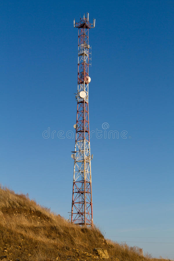 Telecommunication tower on a hill. Antenna mast isolated on blue sky background. Telecommunication tower on a hill stock photography