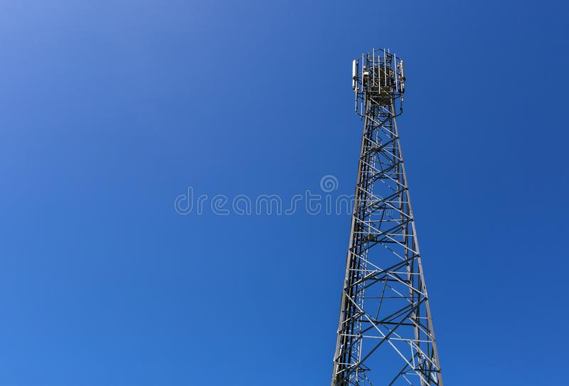 Telecommunication tower or mast with microwave, radio panel antennas, outdoor remote radio units, power cables, coaxial stock photos
