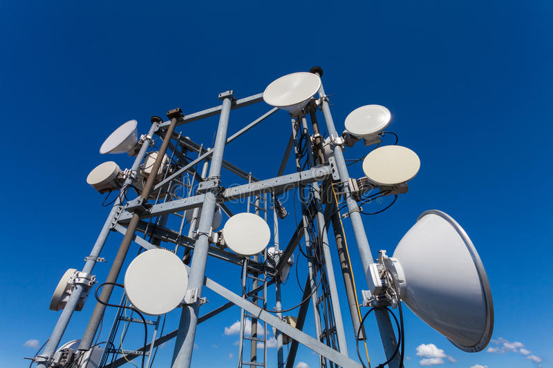 Telecommunication tower with microwave antennas and satellite dishes with cables and fiber optic royalty free stock photos