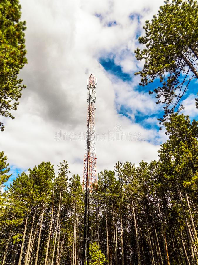 Telecommunication tower of mobile telephone network base station with smart cellular antennas radiating strong signal royalty free stock image