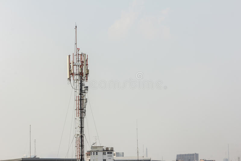 Telecommunication tower with multiple antennas and data transmit. Ters with beautiful city in the background and wide mountain area stock photo