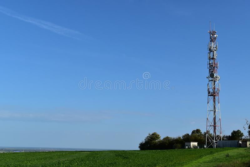 Telecommunication tower with radio antennas in a green environment. stock image