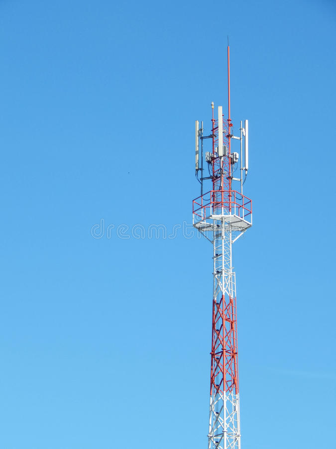 Telecommunication tower red and white with blue sky. Background stock photo
