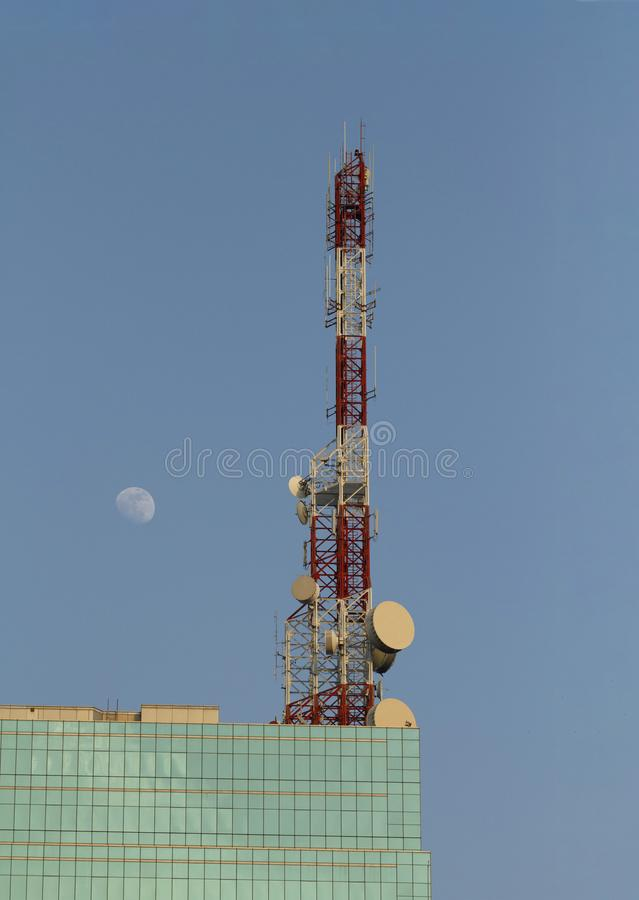 Telecommunication tower. With moon on blue sky royalty free stock photo