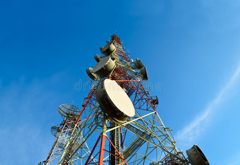 Telecommunication towers with antennas. Against blue sky stock images