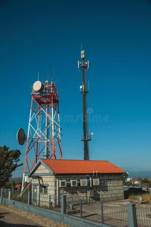Telecommunication towers on a base transceiver station. Telecommunication cellular network towers with antennas on a base transceiver station, in a sunny day at stock photography
