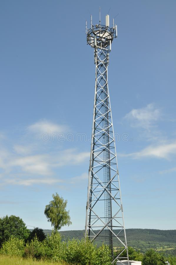 Telecommunication towers on a green hill royalty free stock images