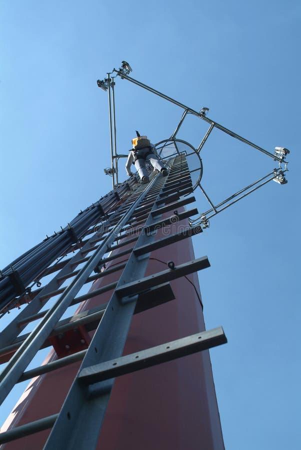 Telecommunication worke. A telecommunication tower with a worker climbing royalty free stock photo