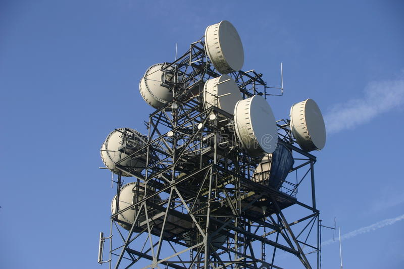 Telecommunications mast. Metal telecommunications mast with aerials and dishes. Background of blue sky with white aircraft contrails stock photo