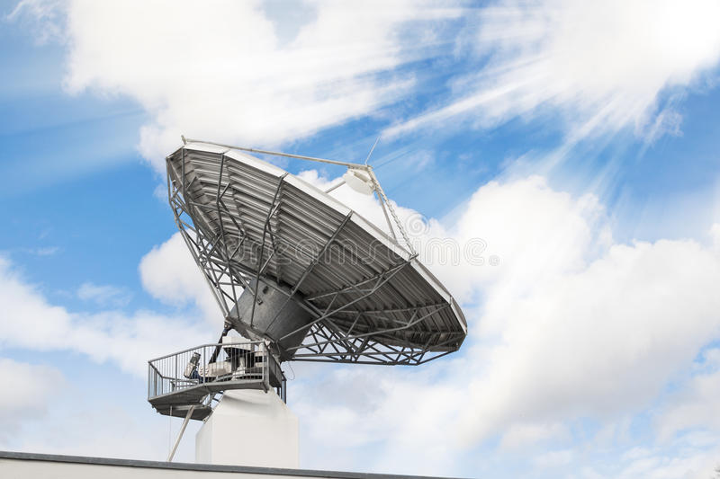 Telecommunications radar parabolic radio antenna. As part of global communication technology stations system against sunny sky with sun rays sunbeams. Toned and stock image