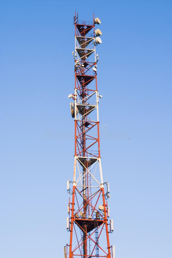 Telecommunications tower against a blue sky .  Radio and satellite pole. Communication technology. Telecommunication industry. Mob stock images