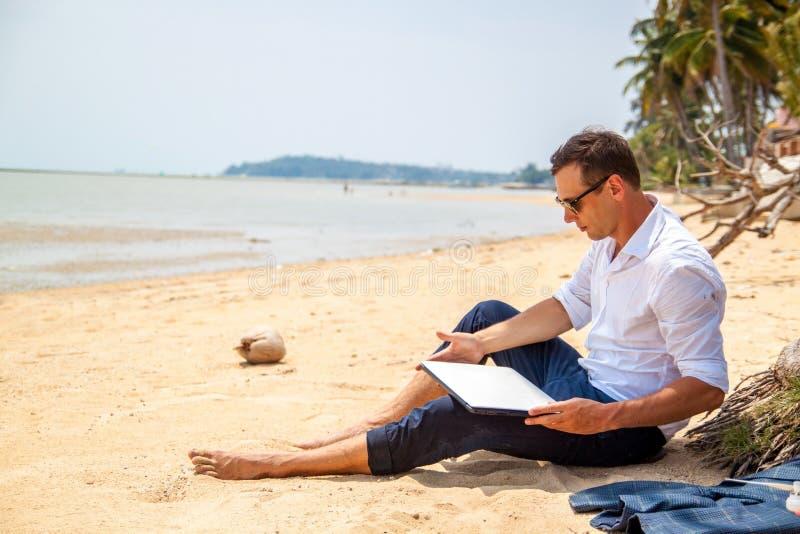 Telecommuting aff?rsmannen som kopplar av p? stranden med b?rbara datorn och, g?mma i handflatan, freelancerarbetsplatsen, dr?m-  royaltyfri fotografi
