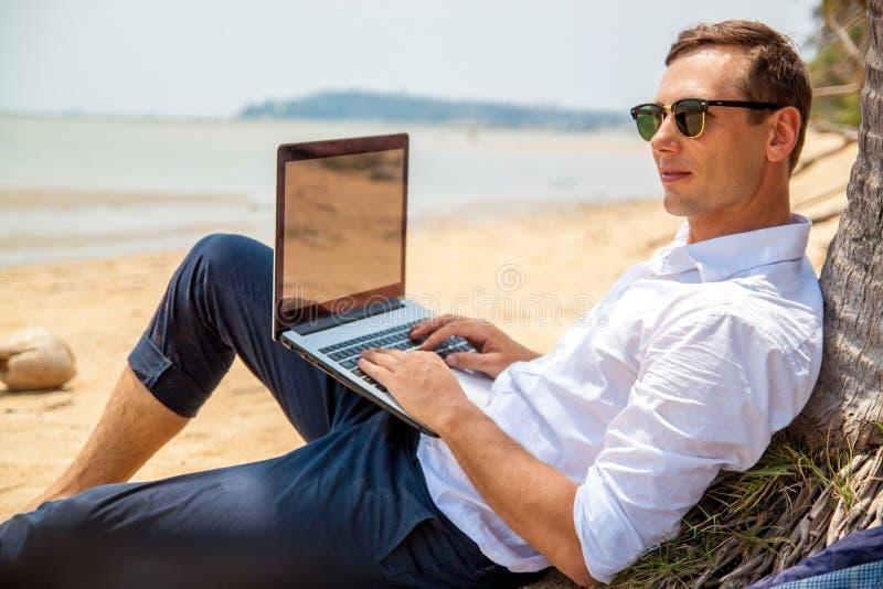 Telecommuting aff?rsmannen som kopplar av p? stranden med b?rbara datorn och, g?mma i handflatan, freelancerarbetsplatsen, dr?m-  arkivbild