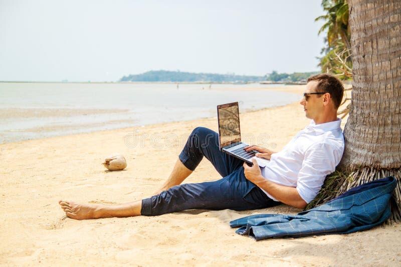 Telecommuting aff?rsmannen som kopplar av p? stranden med b?rbara datorn och, g?mma i handflatan, freelancerarbetsplatsen, dr?m-  royaltyfria bilder