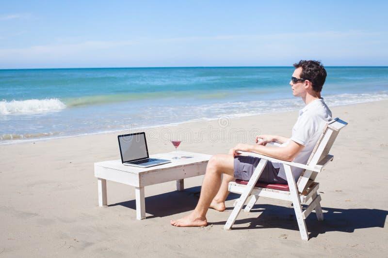 Teleconmutación, hombre de negocios con el ordenador portátil en la playa imagen de archivo libre de regalías