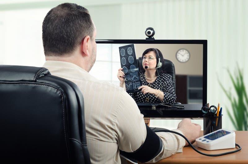 Teledoctor que mira el rayo del cerebro x mientras que mide la presión arterial fotos de archivo
