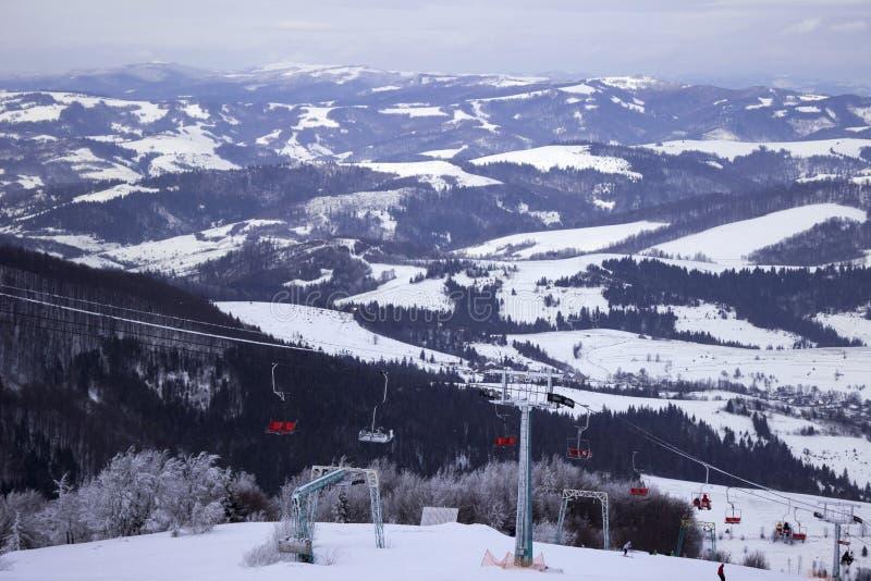 Teleférico con los esquiadores en las montañas, vacaciones de invierno, ucraniano Cárpatos imagen de archivo