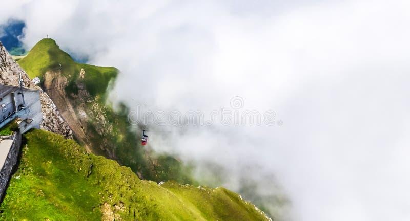 Teleférico da vista excitante que escala acima o penhasco Craggy íngreme na atmosfera grossa da névoa do rastejamento fotografia de stock