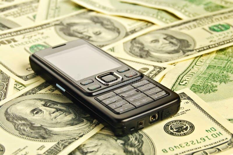 Telefon auf dem Geld lizenzfreie stockbilder