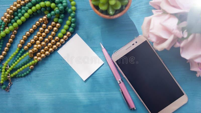Telefon, Blumen, ein Stift und ein Notizbuch Noch Leben 1 Draufsicht, das Konzept des Arbeitsplatzes stockbild