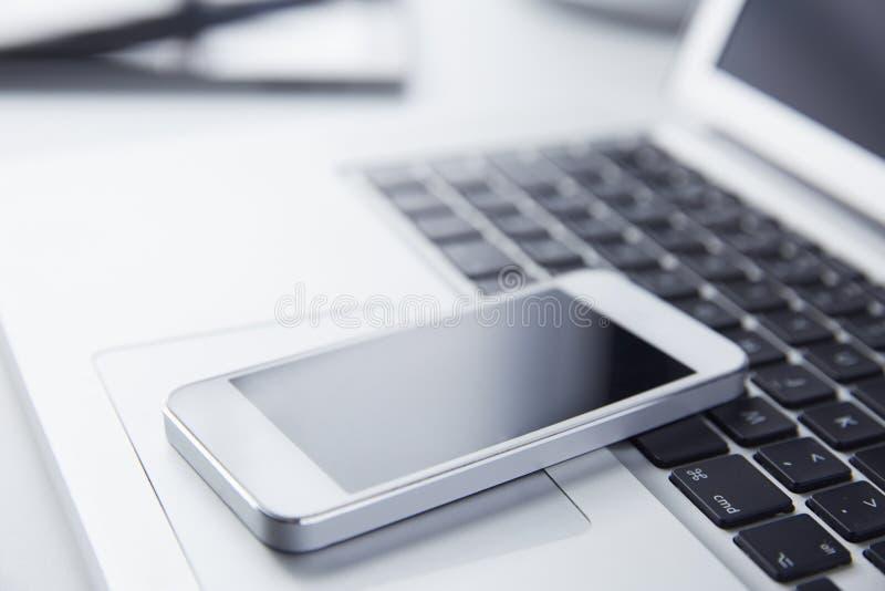 Telefon, das auf einer Laptop-Computer stillsteht stockfotografie