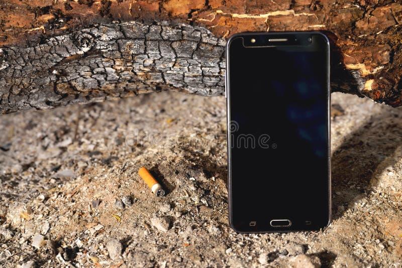 Telefon in einer Feueraschbrennholzstaubseitensonnenlicht-Zigarettenkippezigarette brannte Klotz stockbild