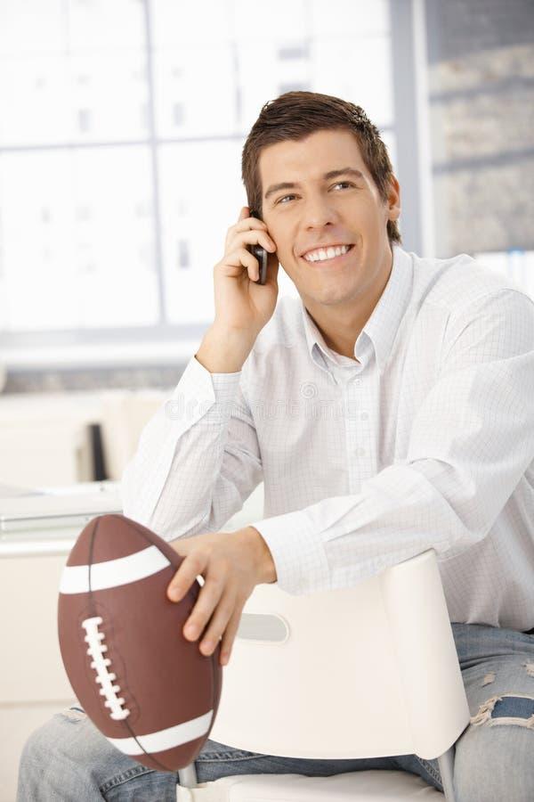 telefon för holding för affärsmanfotboll lycklig royaltyfri fotografi
