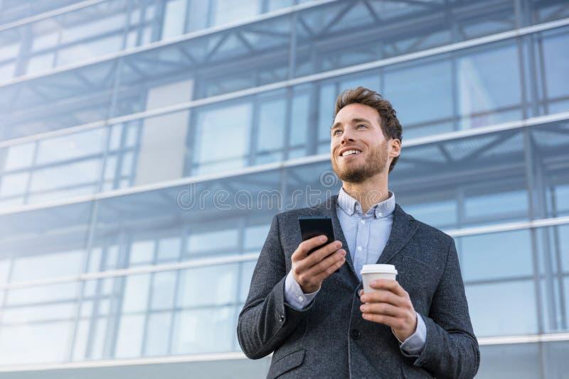 Telefon för innehav för affärsman som dricker kaffe på bankkontoret som tänker av framtiden Affärsman som drömmer av karriärhopp arkivfoton