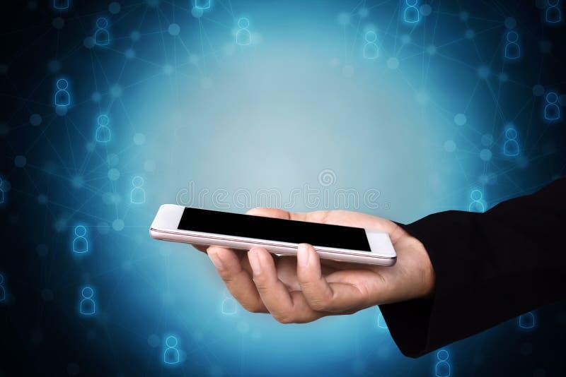 Telefon för innehav för hand för affärsman smart med nätverkandefolksymbolen arkivfoton