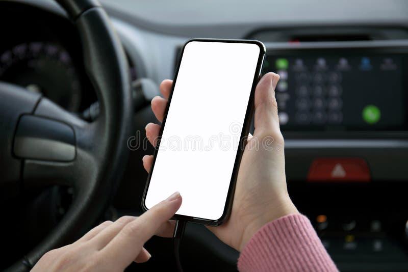Telefon för kvinnahandinnehav med den isolerade skärmen i bilen fotografering för bildbyråer