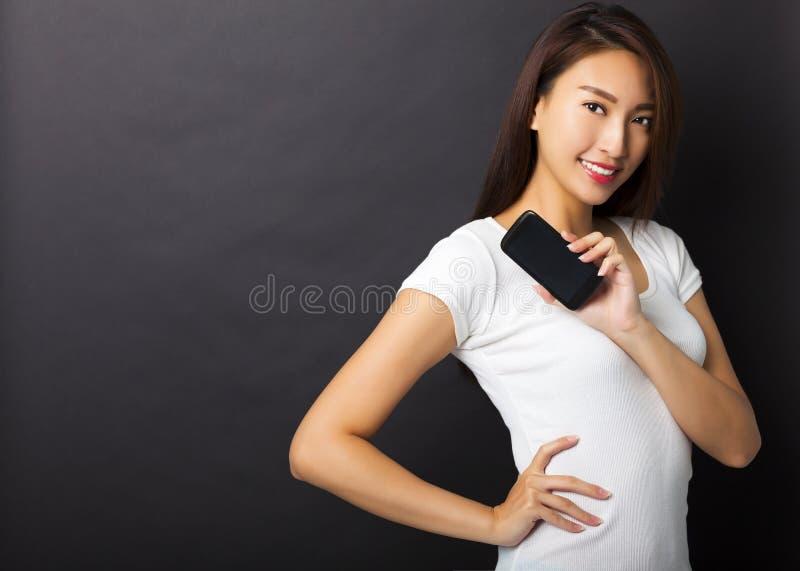 telefon för visning för ung kvinna smart med svart bakgrund arkivbilder